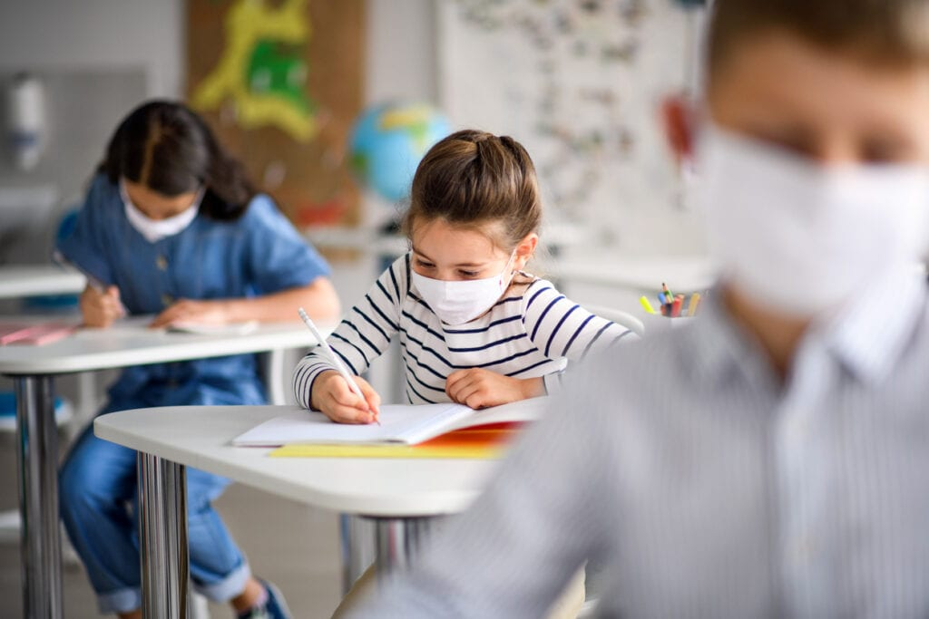 Children with face mask back at school after covid 19 quarantine and lockdown